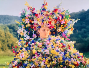 Midsommar, character Dani (Florence Pugh) sadly looks on while adorning a floral dress